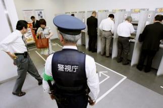 銀行のATMの前に警官の姿も…(写真:共同通信社)