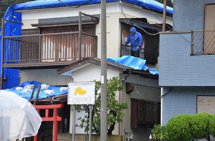 千葉県では台風後も悪天候が続き、屋根のブルーシートを住民自ら修復(写真:時事通信フォト)