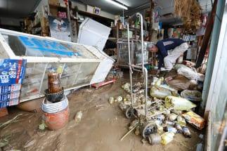8月の九州北部豪雨にて、浸水した雑貨店を片づける店主(写真:時事通信フォト)