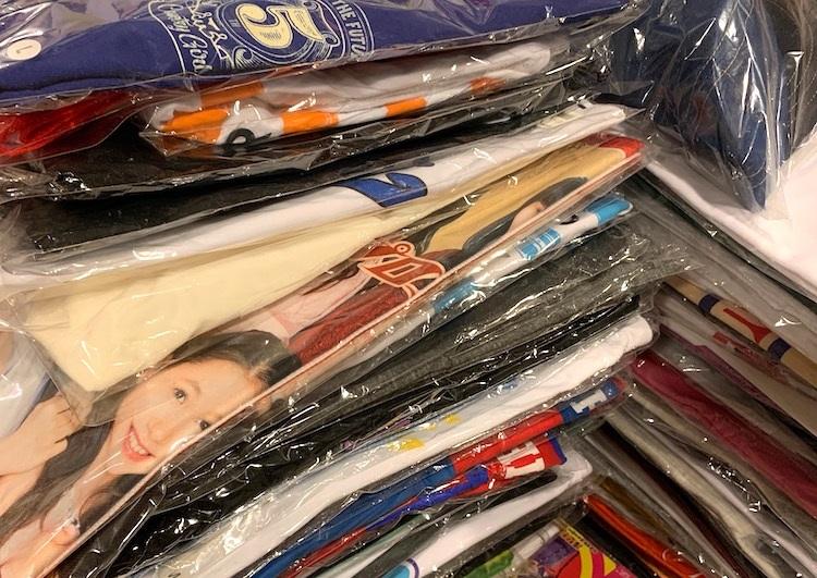 あるアイドルファンの部屋に積み重ねられたグッズのTシャツたち