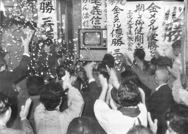 1964年当時、テレビで東京五輪を観戦する人々(写真:共同通信社)