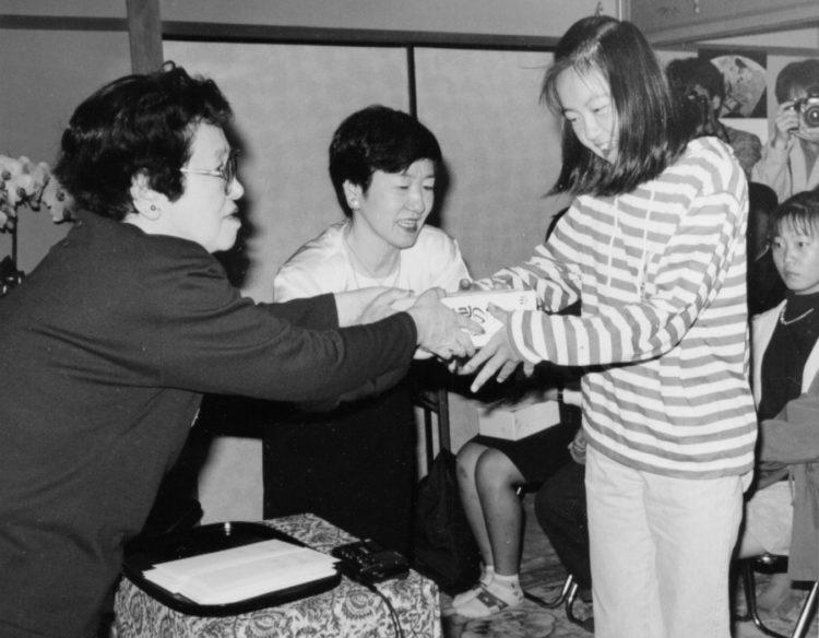 山崎豊子さんが作中に忍ばせた「遺言書」とは(「山崎豊子文化財団」の奨学生第1期生に奨学金と著書を手渡す山崎さん(写真左)と野上孝子さん(写真中央))(1994年)