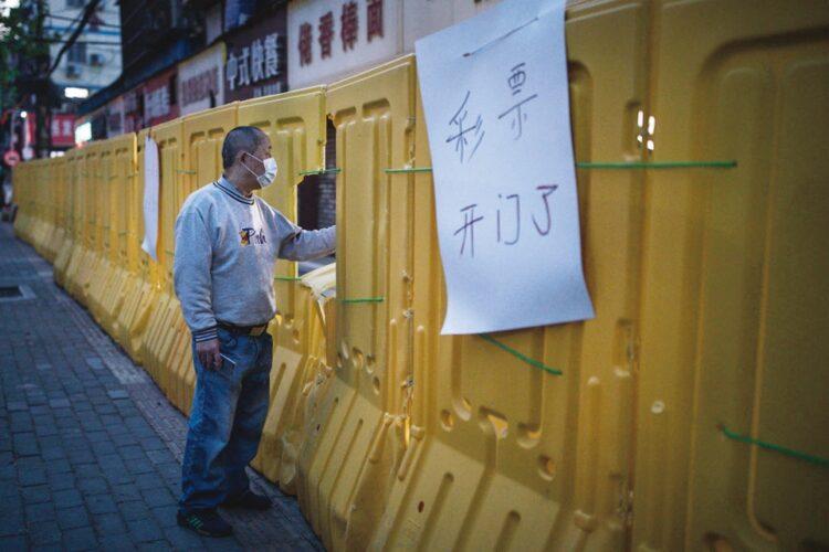 2020年4月、コロナウイルスが広がった武漢で、団地に巡らされたバリケードの窓から宝くじを購入する男性(Getty Images)