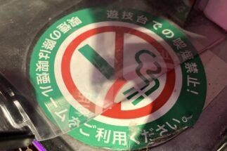 かつて灰皿が置いてあったパチンコ台の横には禁煙化を告知するステッカーが貼ってある