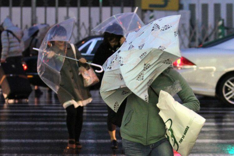 台風並みの暴風と雨の中、傘を差して歩く人々(写真/2012年4月、時事通信フォト)