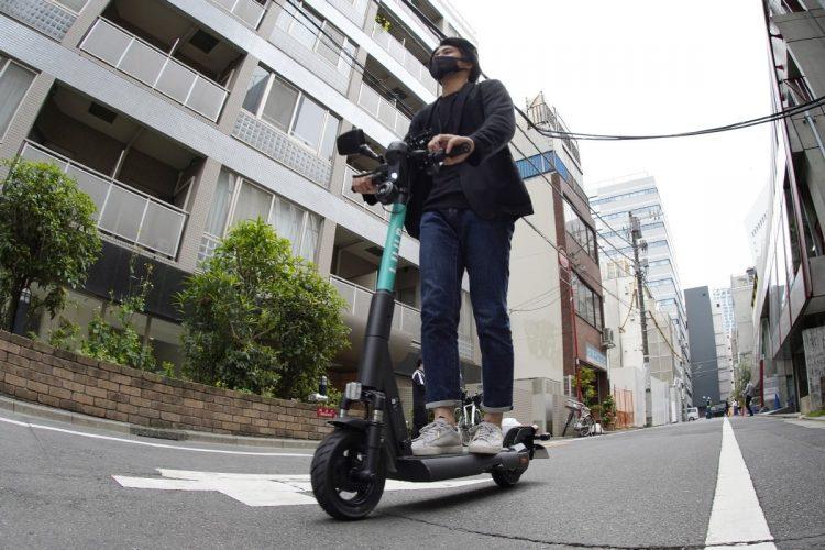 電動キックボードのシェアリングサービスも人気。特例措置としてサービスエリア内ではヘルメットなしで公道を走ることができる(時事通信フォト)